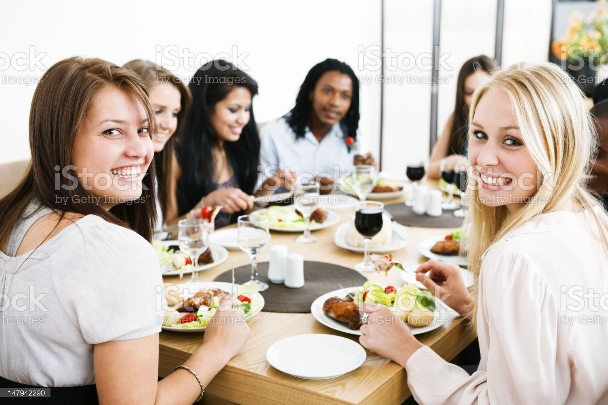 Happy group of young people round dinner table royalty-free stock photo