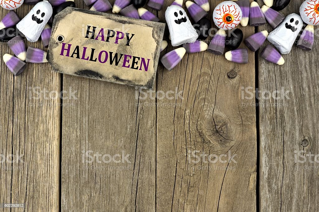Happy Halloween tag with candy top border over aged wood stock photo