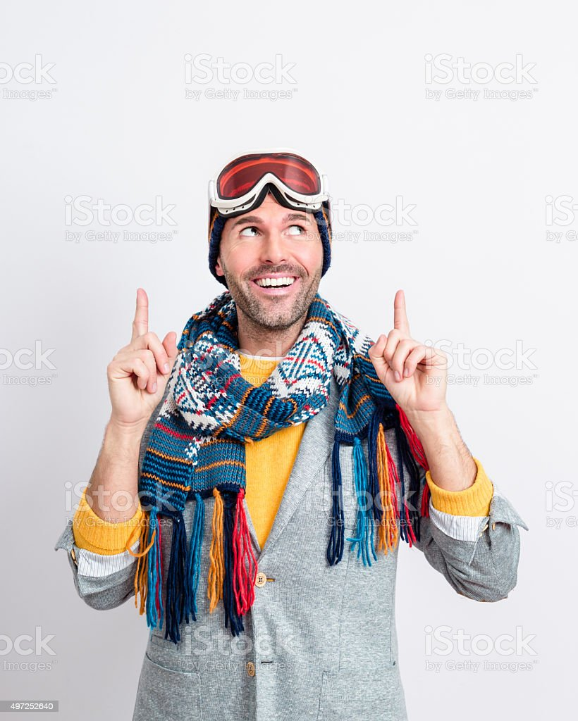 Happy handsome man in winter outfit pointing at copy space stock photo