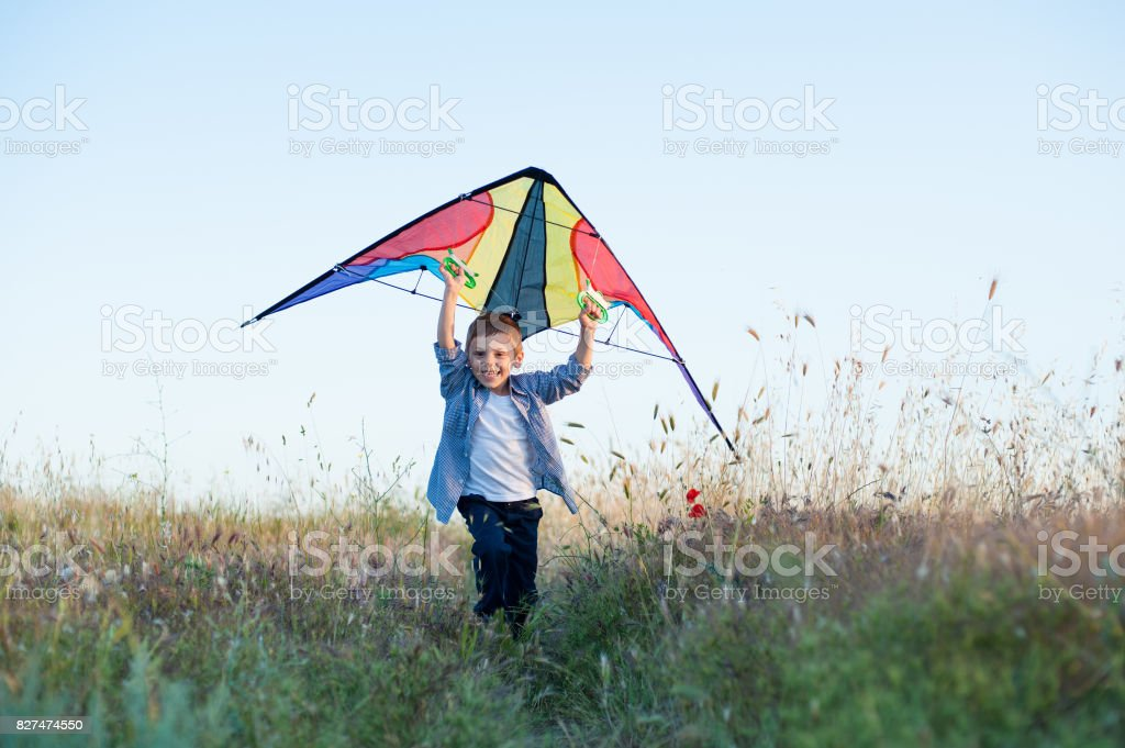 happy handsome small boy running with colorful kite in his hands overhead stock photo