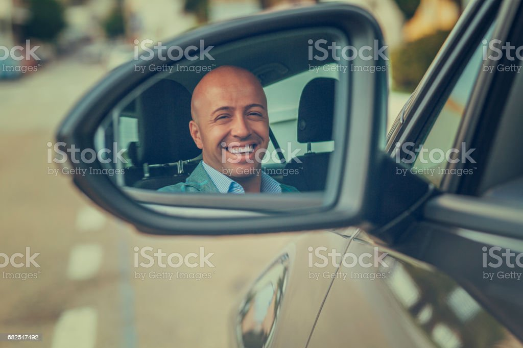 Happy handsome young business man driver in his car looking back to the road side view mirror. Positive human face expression emotions. Safe trip journey driving concept stock photo