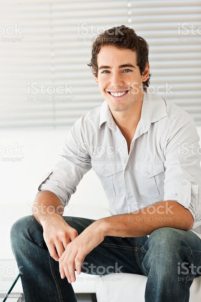 Happy handsome young man at home stock photo