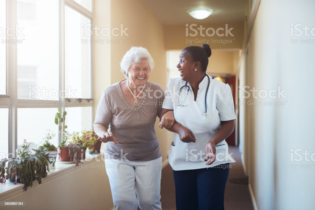 Happy healthcare worker and senior woman talking together stock photo