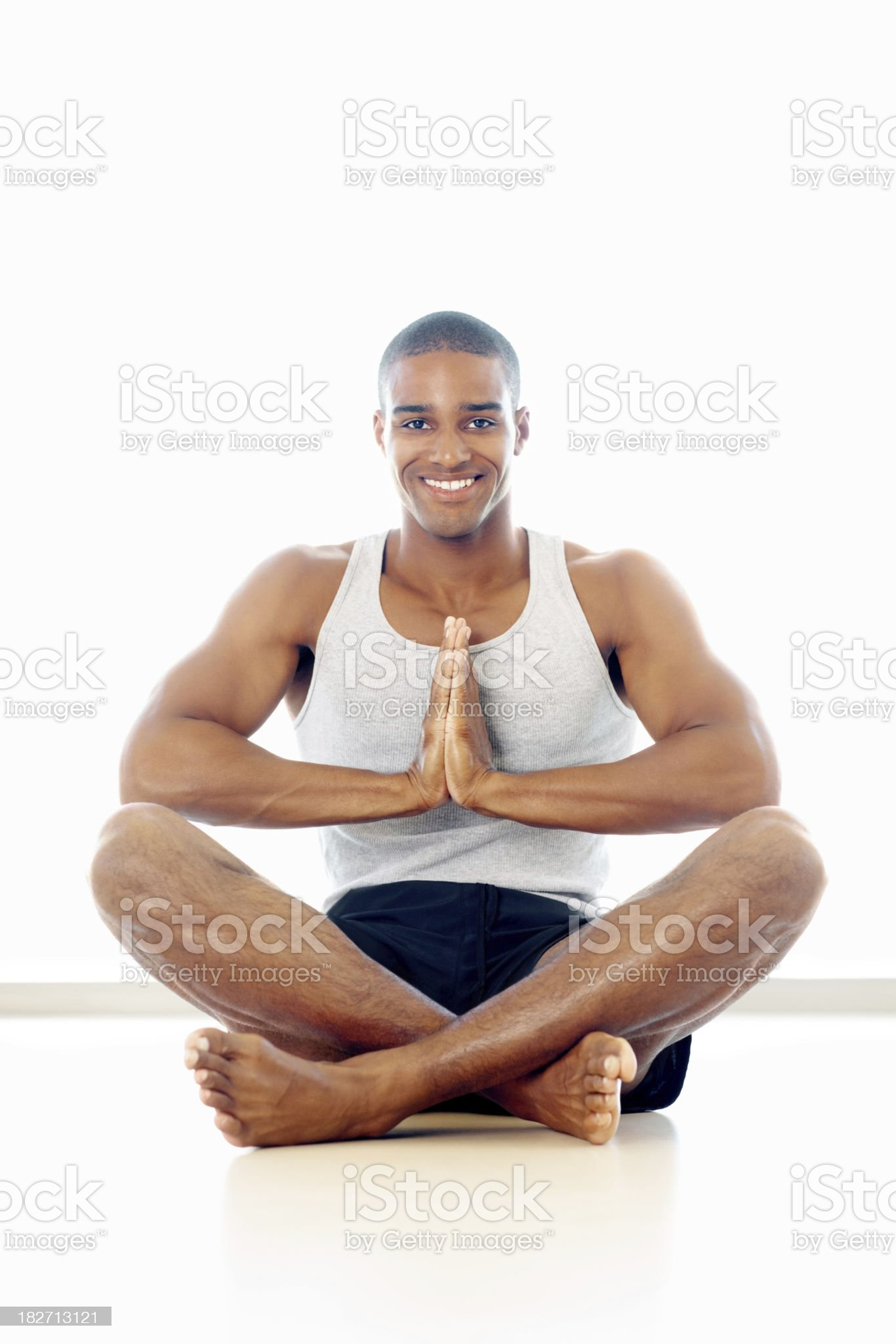 Happy healthy guy meditating in a yogatic pose on white royalty-free stock photo