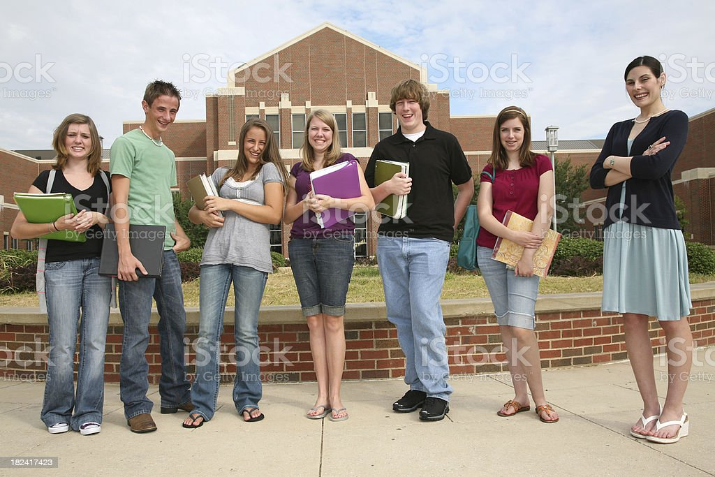 Happy High Schoolers With Teacher Outside School Building royalty-free stock photo