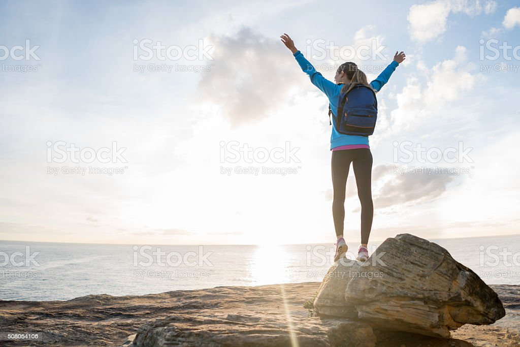 Happy hiker reaching the top stock photo