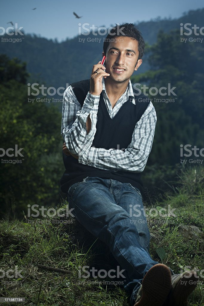 Happy Himachali young man of Indian ethnicity talking on phone stock photo