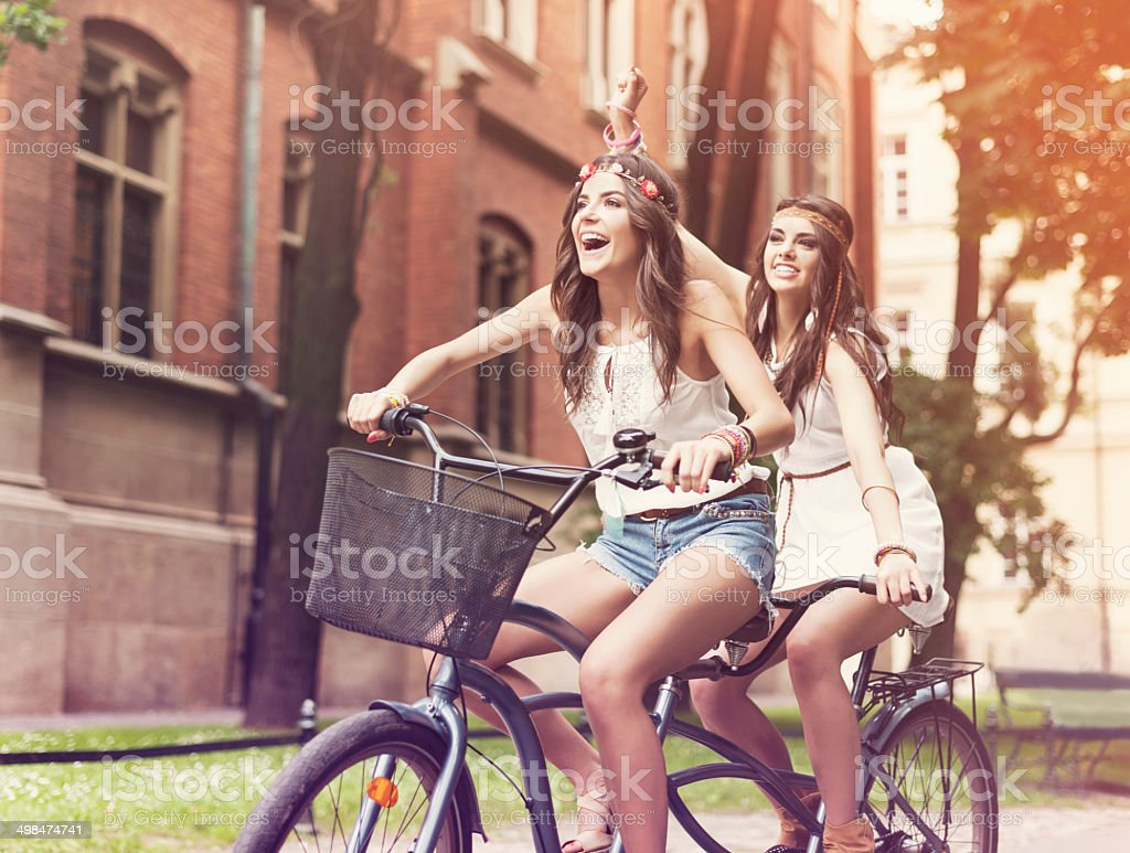 Happy hippie woman riding a tandem in the park stock photo
