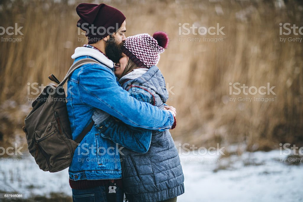 Happy hipster couple hugging near winter reeds stock photo