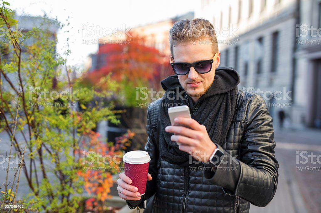 Happy hipster having coffee and using smartphone stock photo