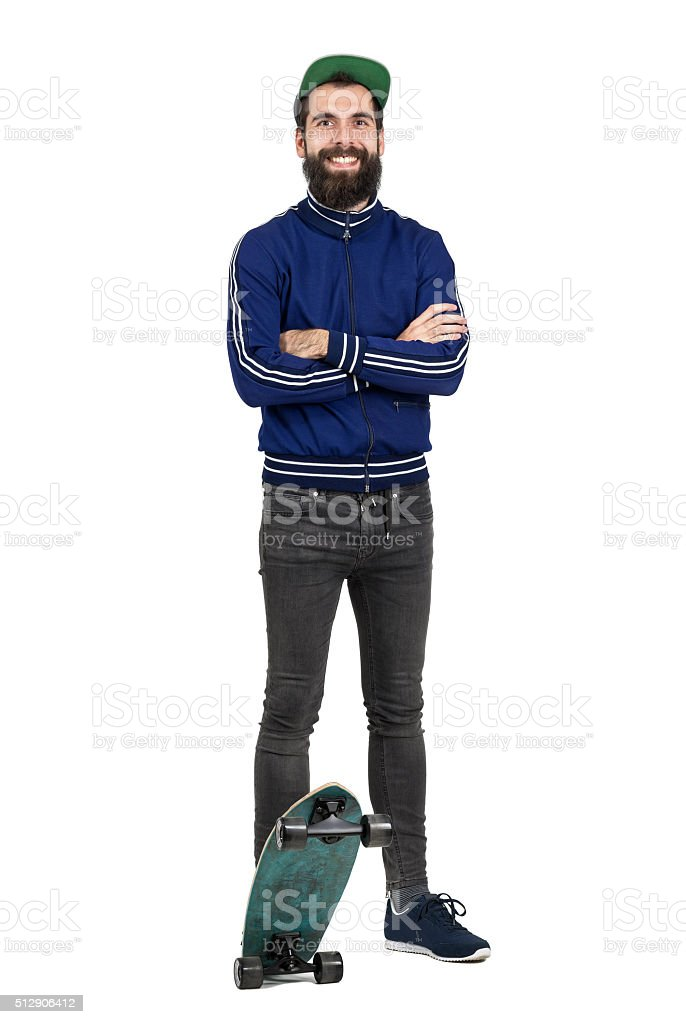 Happy hipster in tracksuit jacket and cap smiling at camera stock photo