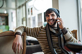 Happy hipster man relaxing while being on the phone.