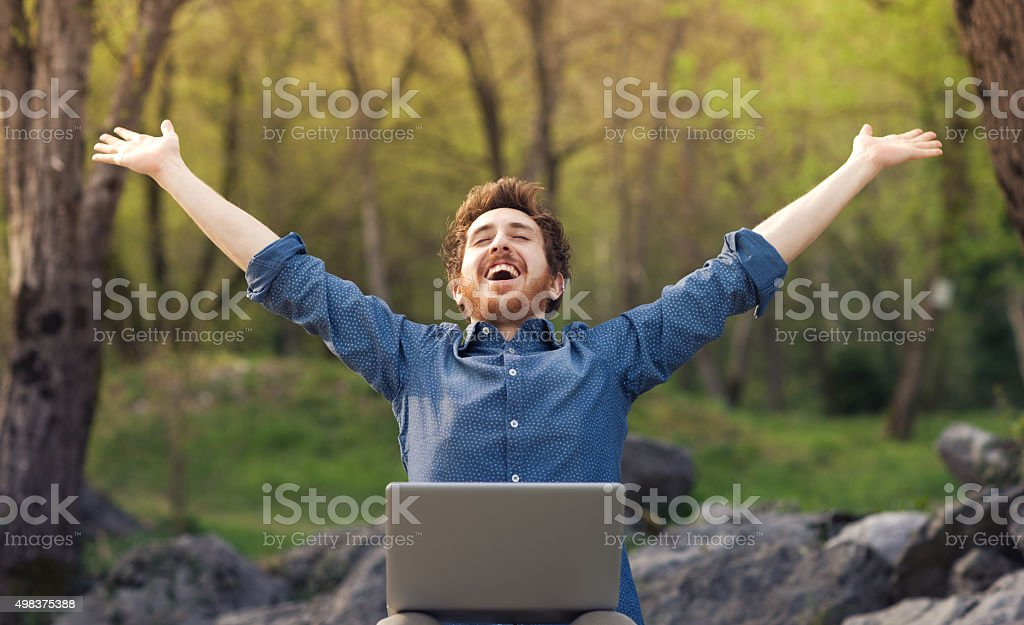 Happy hipster with laptop in the forest stock photo