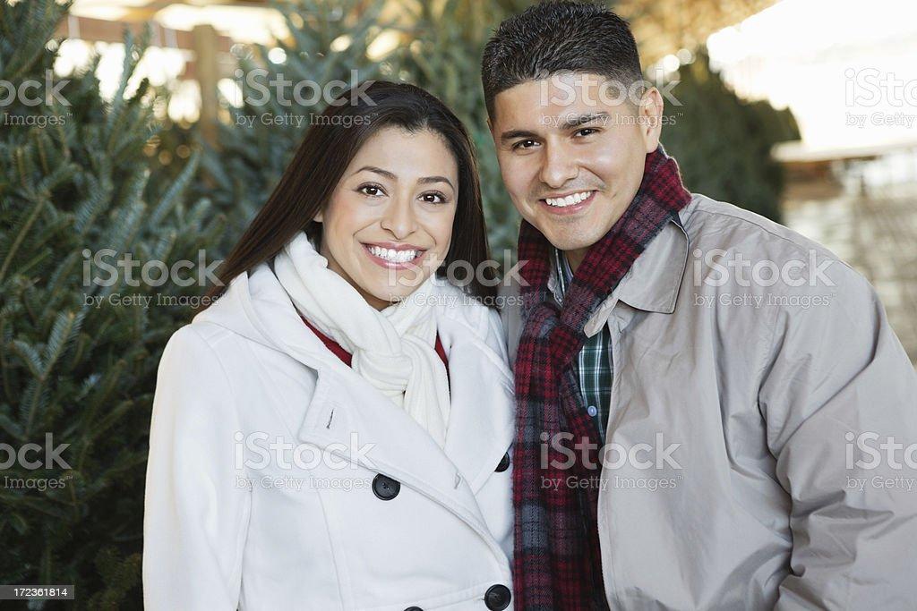 Happy Hispanic couple choosing Christmas tree at farm royalty-free stock photo