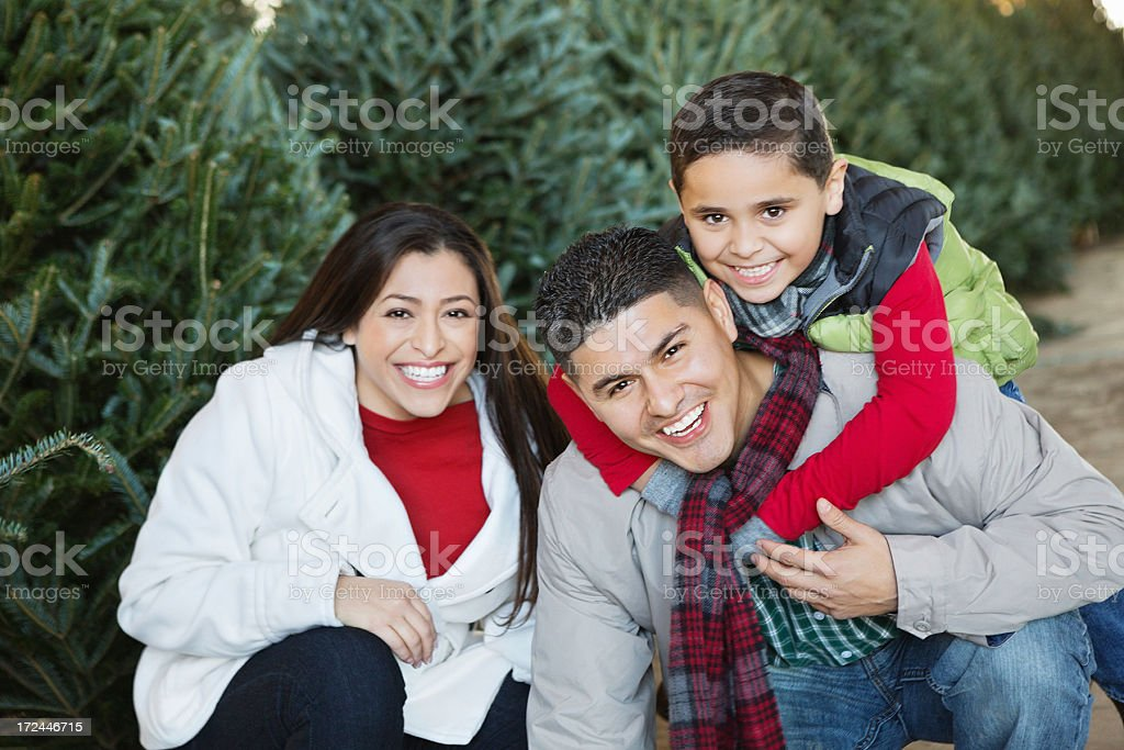 Happy Hispanic family shopping together for Christmas tree stock photo
