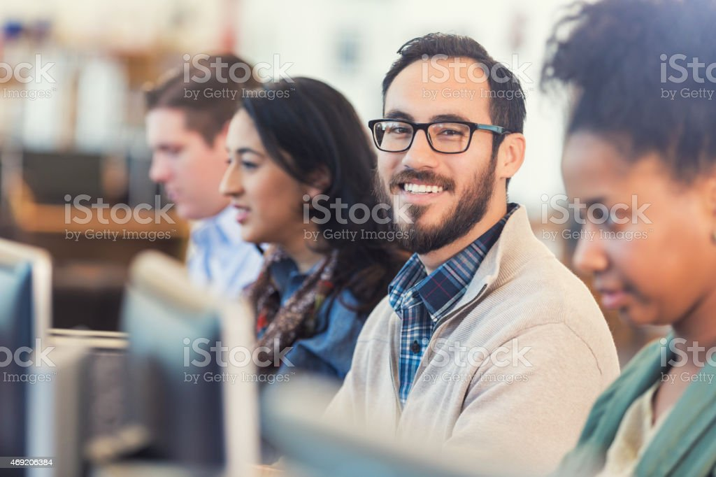Happy Hispanic hipster man using comptuer in college computer class stock photo