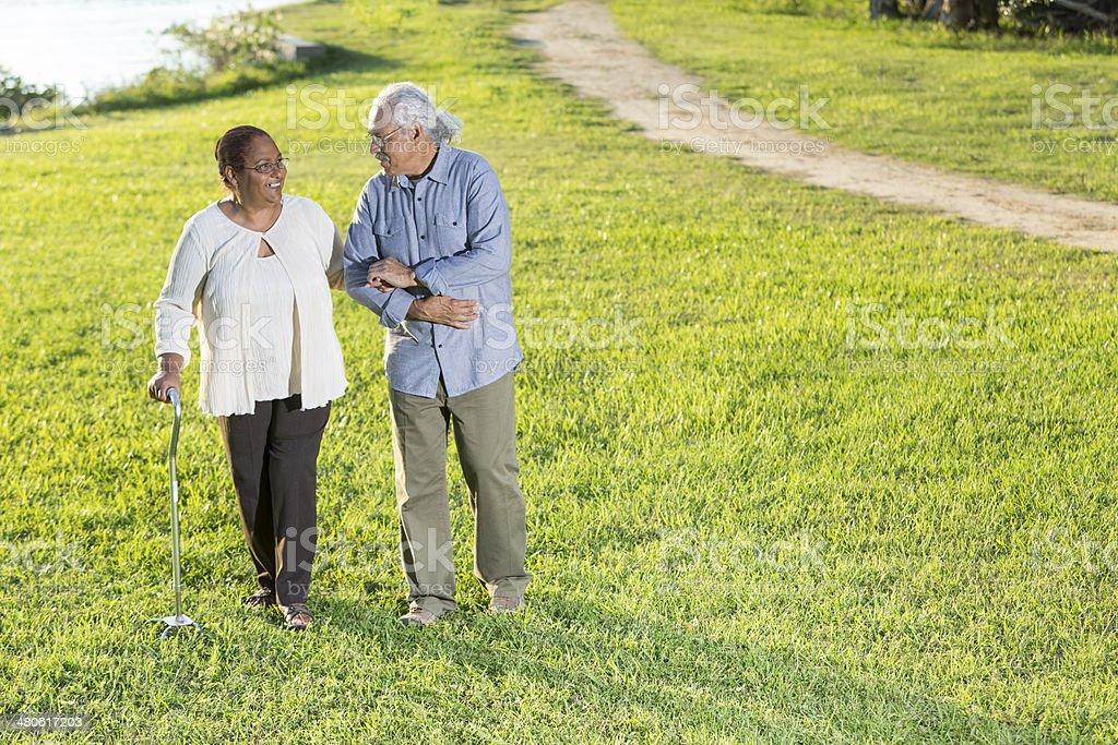 Happy Hispanic senior couple walking in the park. stock photo