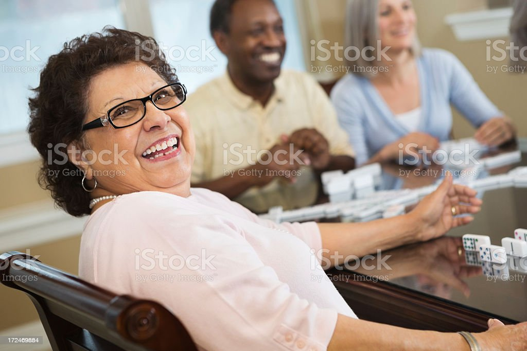 Happy Hispanic senior woman playing dominoes with friends stock photo