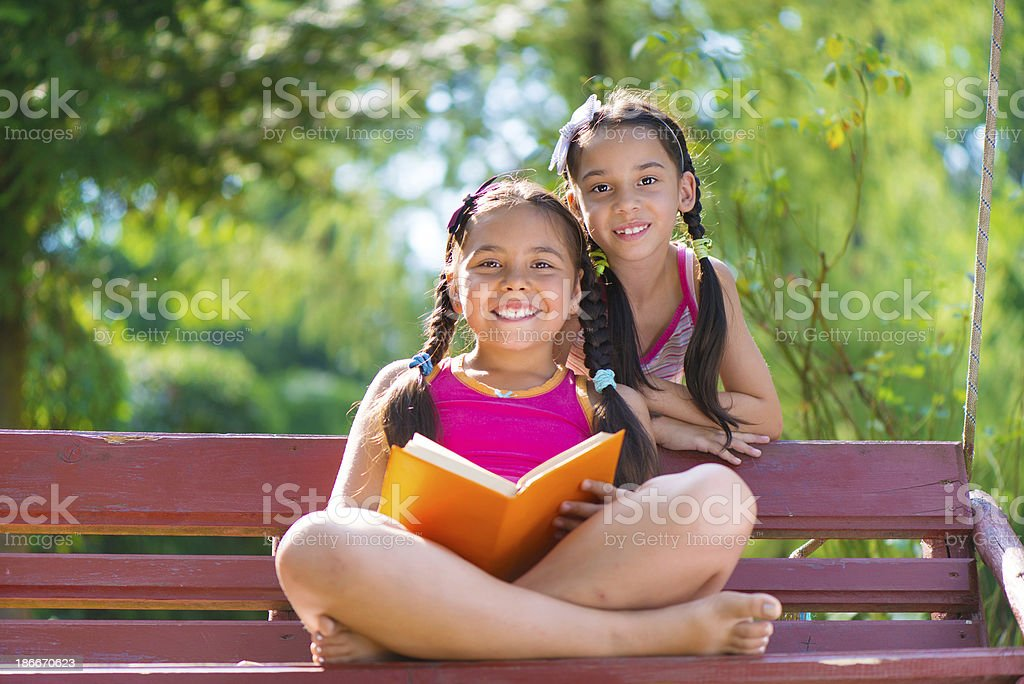 Happy hispanic sisters reading book in summer park royalty-free stock photo