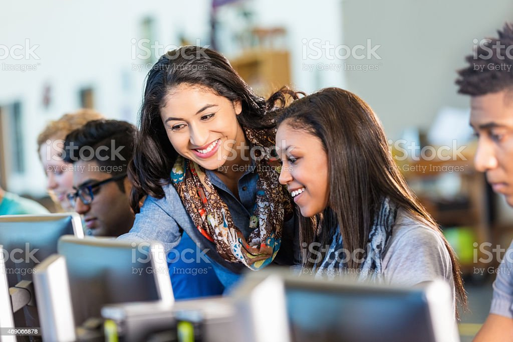 Happy Hispanic teacher assisting high school students with computers. stock photo
