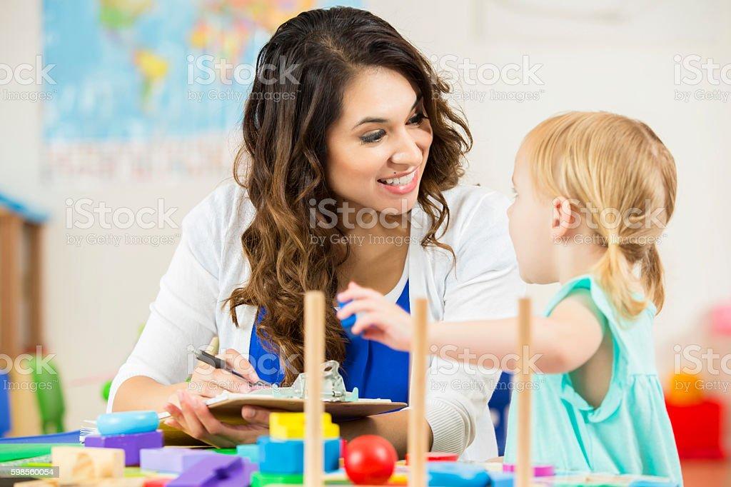 Happy Hispanic teacher smiles at curious little preschooler stock photo