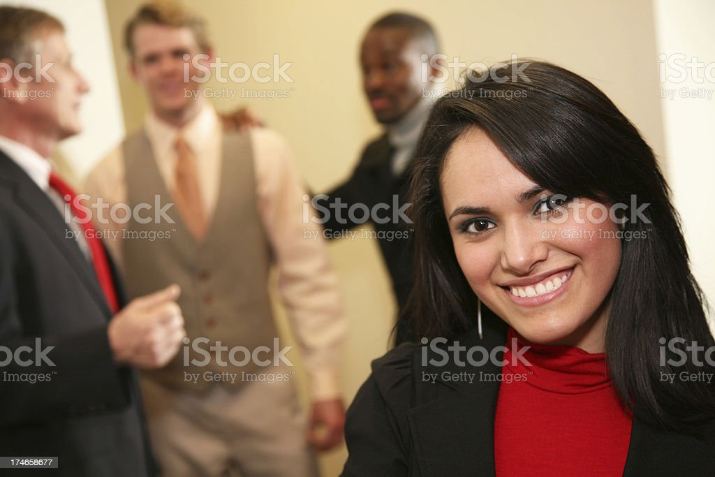 Happy Hispanic Woman at the Office with Workers in Background royalty-free stock photo