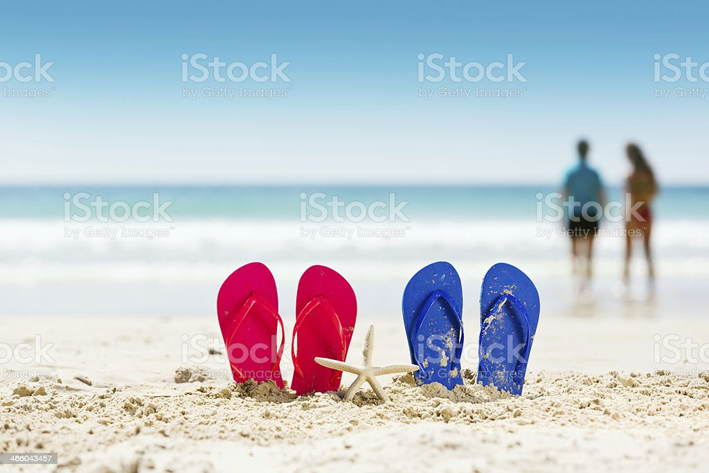 Happy holidays! Flipflop sandals on beautiful beach stock photo