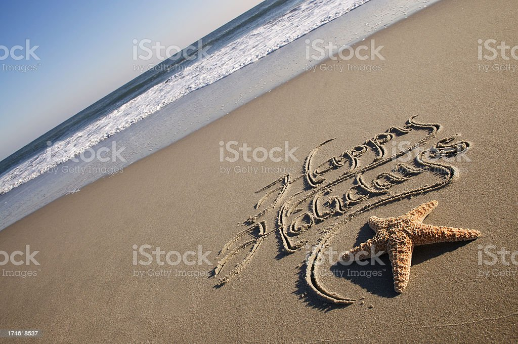 Happy Holidays Greeting Message Tilt with Starfish Smooth Sand Beach royalty-free stock photo