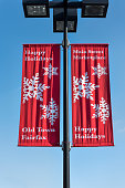 Happy holidays red banner on lamp post in downtown