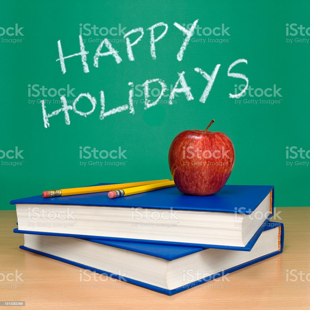 Happy holidays written on a chalkboard behind a desk stock photo