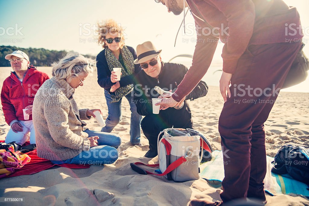 Happy hour for group of friends on beach in spring. stock photo