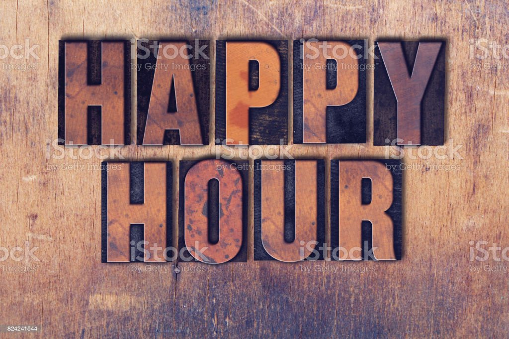 Happy Hour Theme Letterpress Word on Wood Background stock photo