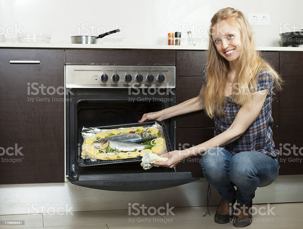 Happy housewife cooking fish  on sheet pan in oven royalty-free stock photo