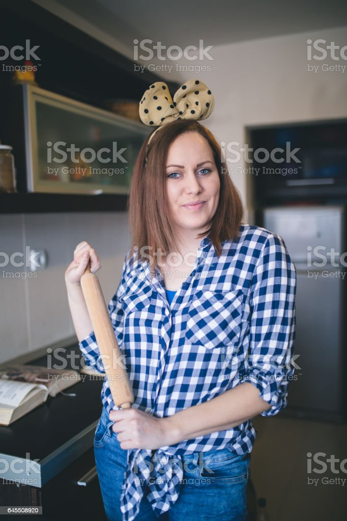 Happy housewife with rolling pin stock photo