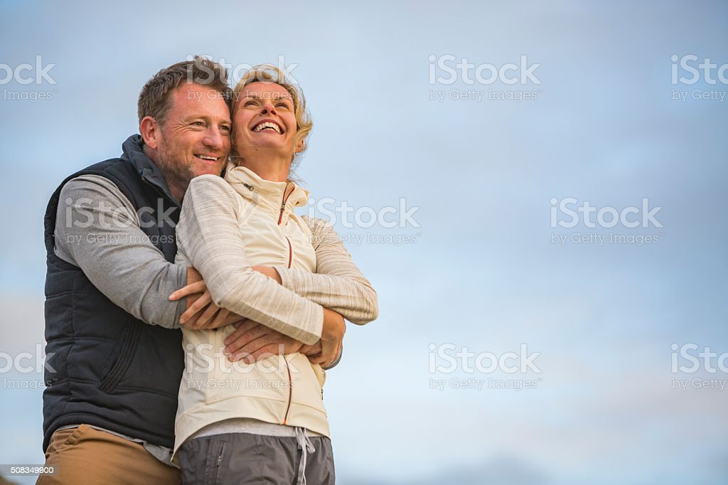 Happy Hugging Middle Aged Active Fit Healthy Beach Couple Outdoors stock photo