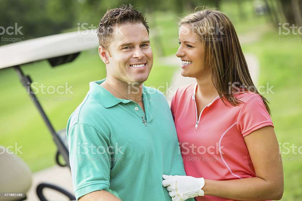 Happy husband and wife playing golf together stock photo