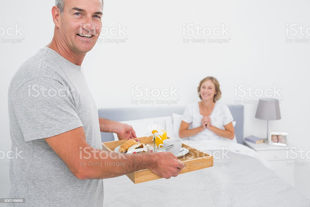 Happy husband bringing breakfast in bed to delighted wife royalty-free stock photo