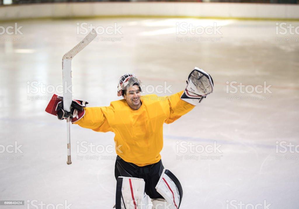 Happy ice hockey goaltender celebrating the success in a rink. stock photo