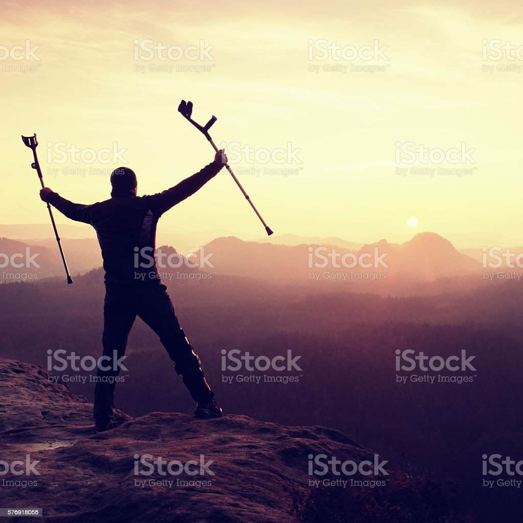Happy ill man celebrate peak achievement. Tourist  with broken leg stock photo