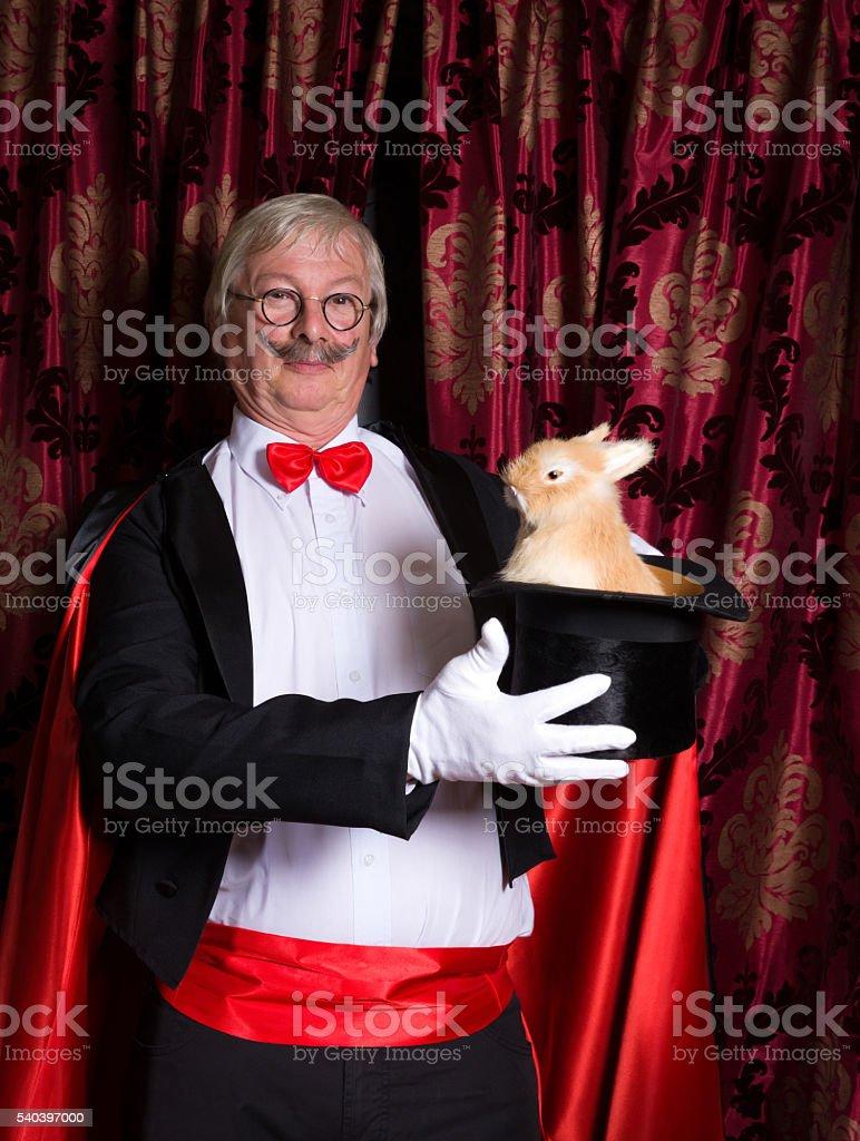 Happy illusionist with rabbit stock photo