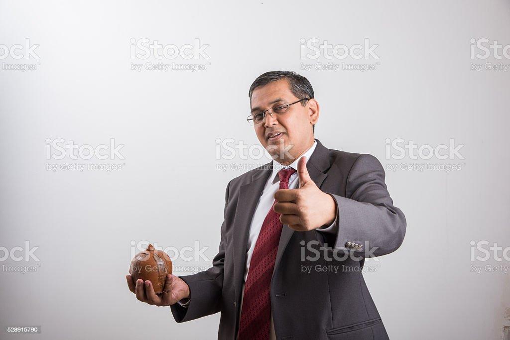 happy indian businessman man holding piggy bank or money box stock photo
