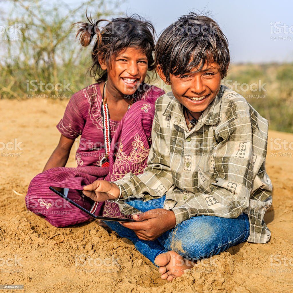 Happy Indian children using digital tablet, desert village, India stock photo