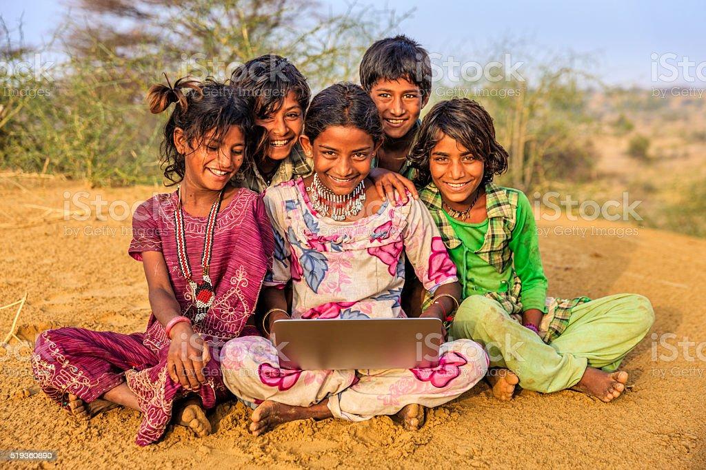 Happy Indian children using laptop, desert village, India stock photo
