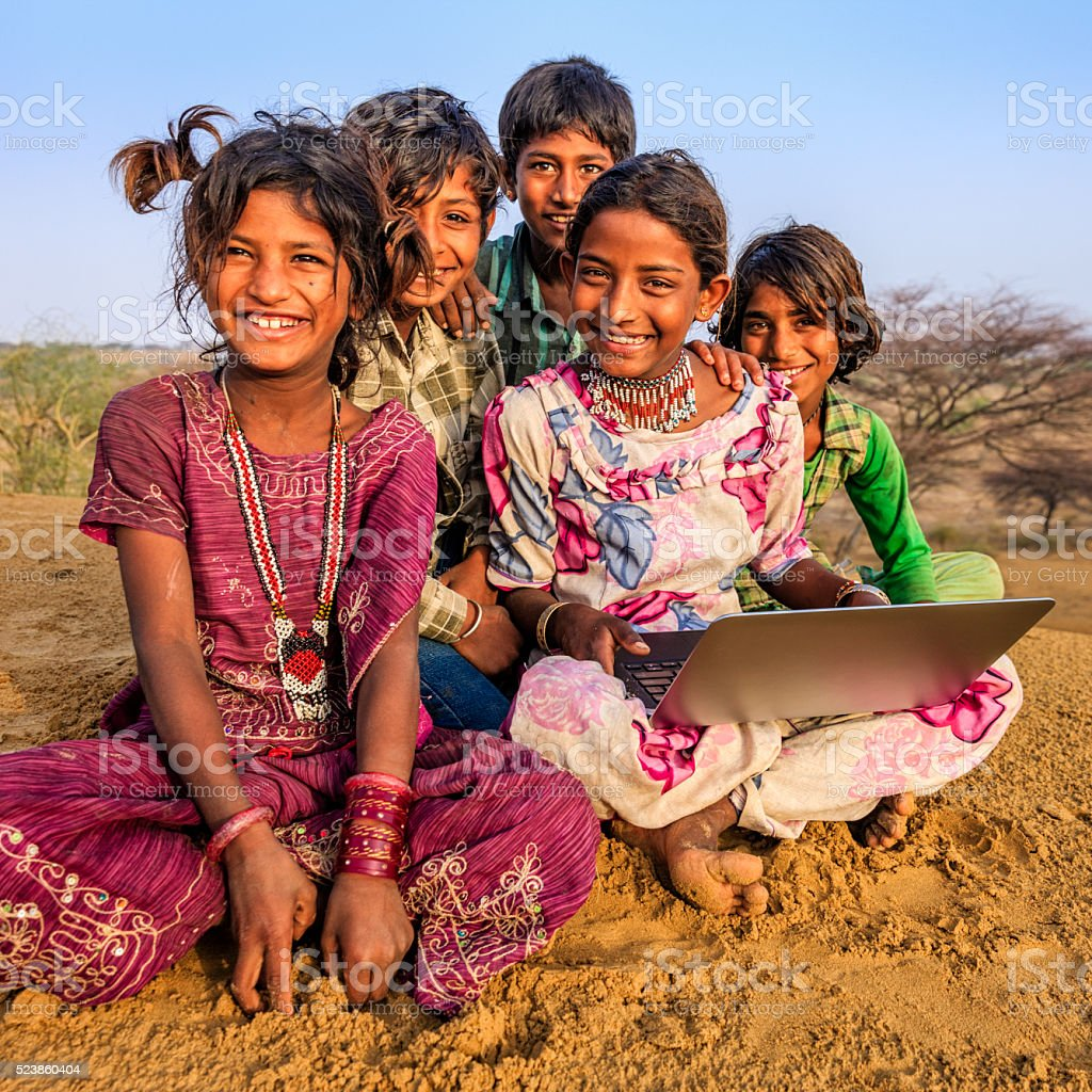 Happy Indian children using laptop, desert village, India stock photo