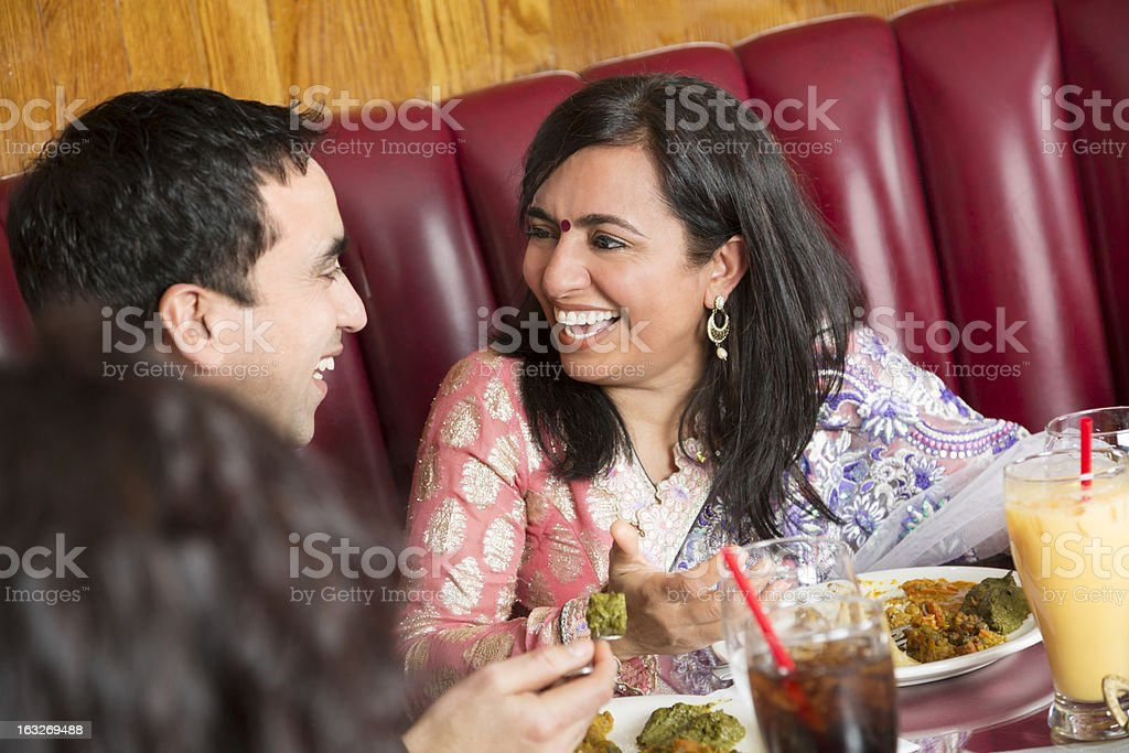 Happy indian couple laughing at the restaurant royalty-free stock photo