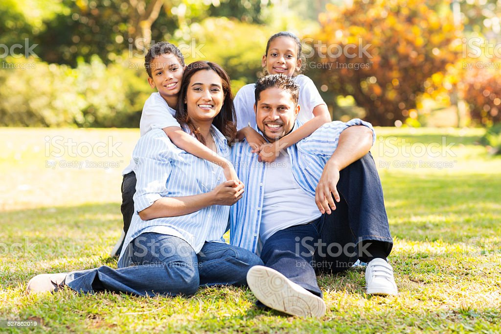 happy indian family sitting on grass stock photo