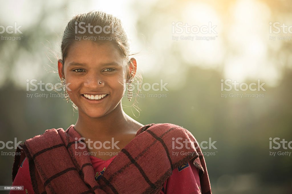 Happy Indian girl giving toothy smile and looking at camera. stock photo