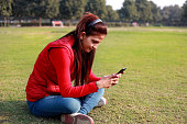Happy Indian girl typing text messaging