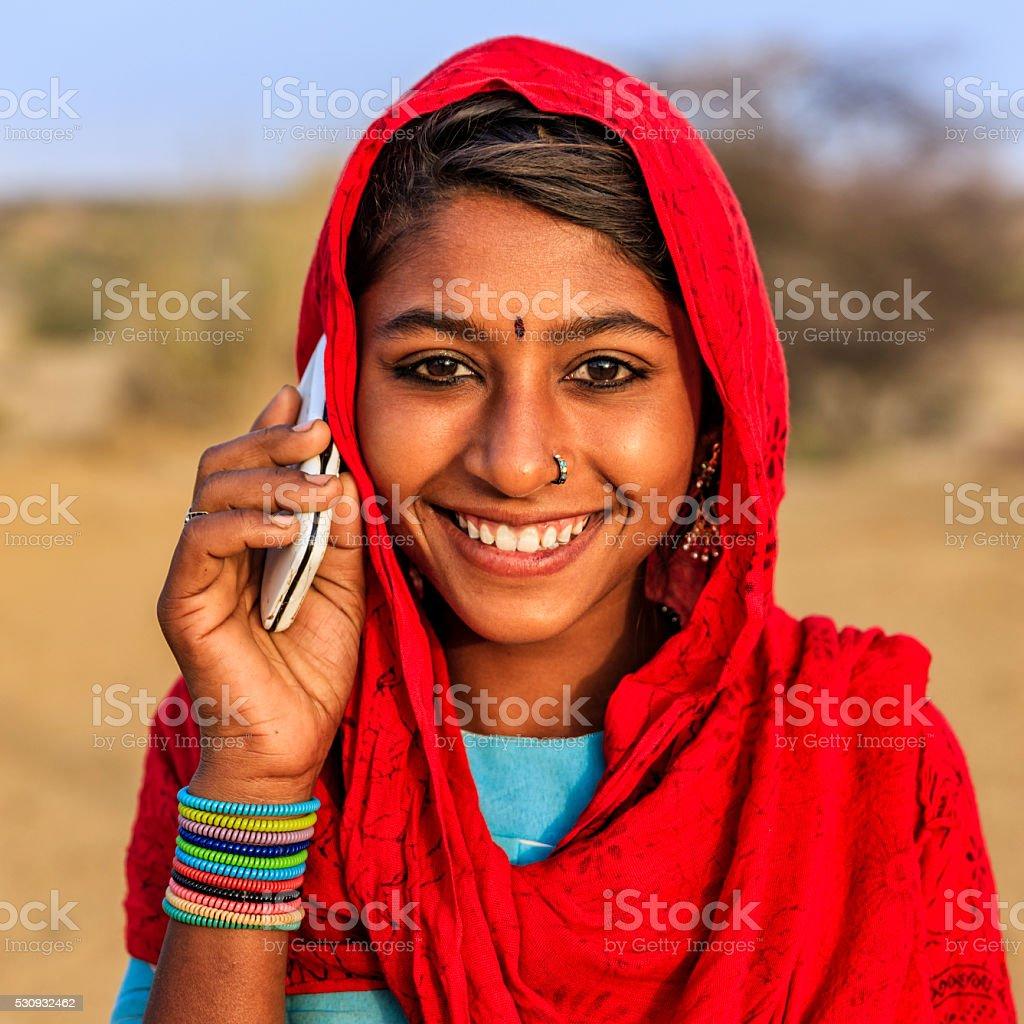 Happy Indian girl using mobile phone in desert village, India stock photo