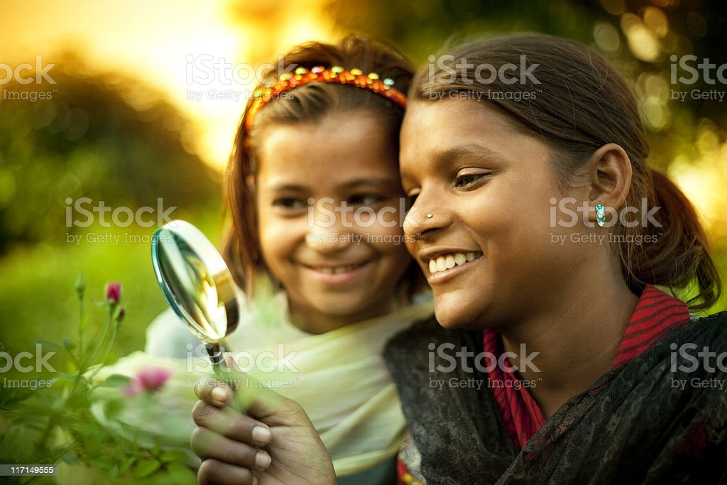 Happy Indian girls exploring something in nature with magnifying glass stock photo